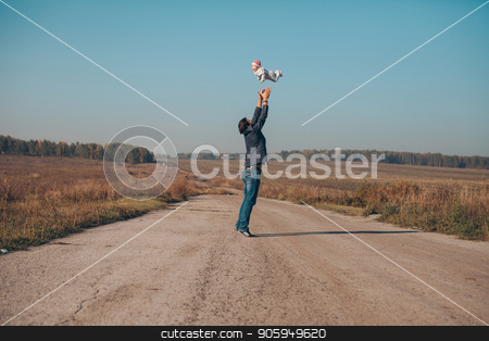A man throws a child up on the road in the middle of the desert stock photo, A man throws a child up on the road in the middle of the desert by aaalll3110