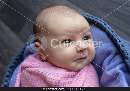 A little child in a pink cap lies on a blue and grey background. Portrait of newborn stock photo, A little child in a pink cap lies on a blue and grey background. Portrait of newborn by aaalll3110