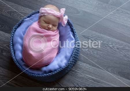 A little child in a pink cap lies on a blue and grey background stock photo, A little child in a pink cap lies on a blue and grey background by aaalll3110