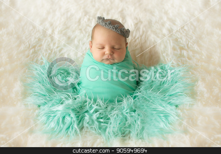 A little child in a greeen diaper lies on a beige background stock photo, A little child in a greeen diaper lies on a beige background by aaalll3110