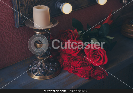 red roses and candle in candlestick on dark background stock photo, red roses and candle in candlestick on dark background by aaalll3110