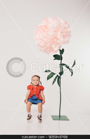 Big flower and little girl in red on white background stock photo, Big flower and little girl in red on white background by aaalll3110