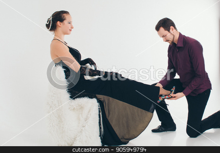 a man puts the girl on his feet shoes. Couple in a suit and dress on white background. A gift for the woman stock photo, a man puts the girl on his feet shoes. Couple in a suit and dress on white background. A gift for the woman by aaalll3110