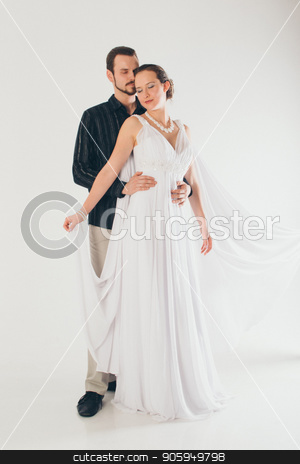 portrait: man in suit and woman in dress on white background. The bride and groom in an isolated photo. Husband hugs wife stock photo, portrait: man in suit and woman in dress on white background. The bride and groom in an isolated photo. Husband hugs wife by aaalll3110