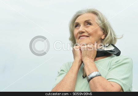 smiling  elderly woman stock photo, Portrait of happy smiling elderly woman posing outdoors by Ruslan Huzau