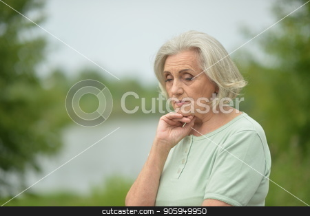 Portrait of sad senior woman stock photo, Portrait of sad senior woman  in summer park by Ruslan Huzau