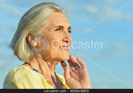 elderly woman posing stock photo, Happy elderly woman posing against blue sky by Ruslan Huzau