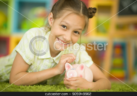 Cute little girl stock photo, Cute little girl with a piggy bank at home by Ruslan Huzau