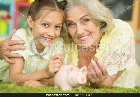 old woman with piggy bank stock photo, portrait of happy beautiful grandmother with granddaughter putting coin into piggy bank by Ruslan Huzau