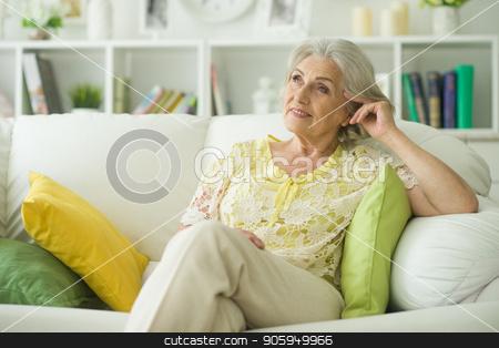 senior woman sitting on sofa  stock photo, Beautiful senior woman sitting on sofa at home by Ruslan Huzau