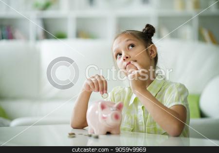 beautiful girl with a piggy bank stock photo, Cute little girl with a piggy bank at home by Ruslan Huzau