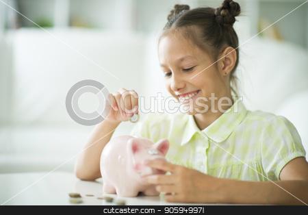 Cute little girl stock photo, Cute little girl with a piggy bank at home by Ruslan Huzau