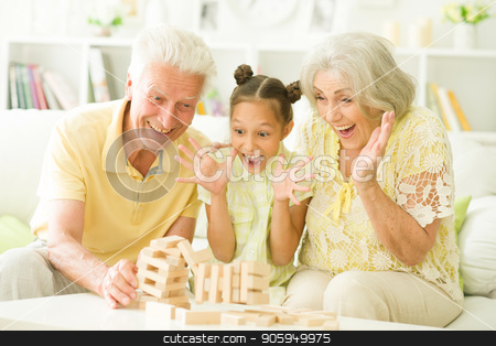 grandparents and granddaughter with wooden blocks stock photo, grandparents and granddaughter sitting at table and playing with wooden blocks by Ruslan Huzau
