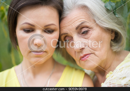 cheerful mother and adult daughter stock photo, Sad senior mother and adult daughter together outdoors by Ruslan Huzau