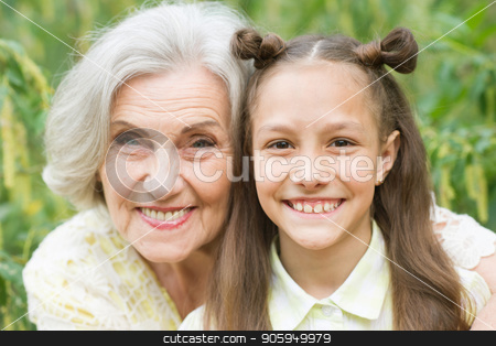 Portrait of grandmother and granddaughter in park stock photo, Portrait of grandmother and granddaughter in summer park by Ruslan Huzau