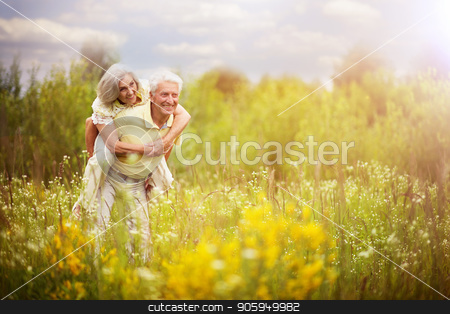 Loving mature couple  in summer park stock photo, Loving mature couple  in summer park. Man piggybacking woman by Ruslan Huzau