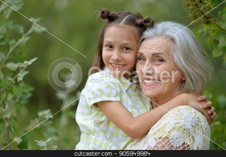 grandmother and granddaughter stock photo, Portrait of grandmother and granddaughter in summer park by Ruslan Huzau