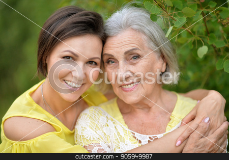 cheerful mother and adult daughter stock photo, cheerful senior mother and adult daughter posing together outdoors by Ruslan Huzau