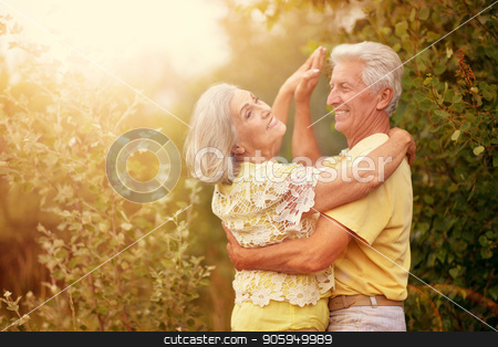 happy mature couple stock photo, happy senior couple smiling and dancing outdoors by Ruslan Huzau