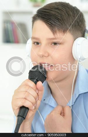Portrait of  boy with microphone  stock photo, Portrait of  boy with microphone singing at home by Ruslan Huzau