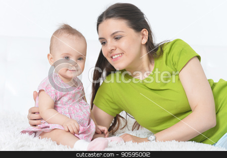 young woman with  baby girl stock photo, young woman with beautiful baby girl posing at home by Ruslan Huzau