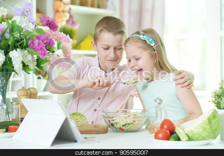brother and sister cooking together stock photo, Cute little brother and sister cooking together at kitchen by Ruslan Huzau