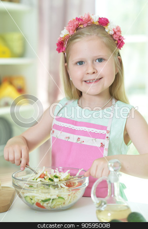 little girl preparing salad on kitchen table stock photo, Cute little girl preparing salad on kitchen table with tablet at home by Ruslan Huzau