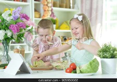 Cute little brother and sister cooking stock photo, Cute little brother and sister cooking together at kitchen by Ruslan Huzau