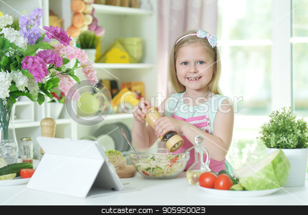 Cute little girl spicing  salad on kitchen table stock photo, Cute little girl spicing  salad on kitchen table with tablet at home by Ruslan Huzau
