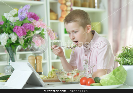 Cute little boy eating salad  stock photo, Cute little boy eating salad and looking at  tablet screen on kitchen table at home by Ruslan Huzau