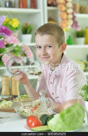 Cute little boy eating salad  stock photo, Cute little boy eating salad on kitchen table at home by Ruslan Huzau