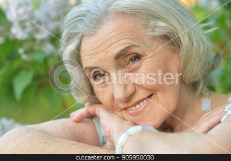 smiling elderly woman posing  stock photo, smiling elderly woman posing  in summer  park by Ruslan Huzau