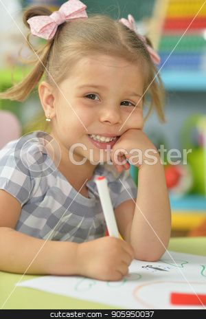 cute little girl drawing with felt pen stock photo, cute little girl drawing with felt pen while sitting at table in her room by Ruslan Huzau