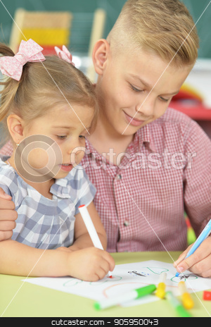 Smiling brother and sister drawing with felt pens stock photo, Smiling brother and sister drawing with felt pens together indoors by Ruslan Huzau