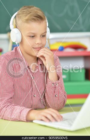 boy with headphones using laptop stock photo, boy with headphones using laptop in classroom by Ruslan Huzau
