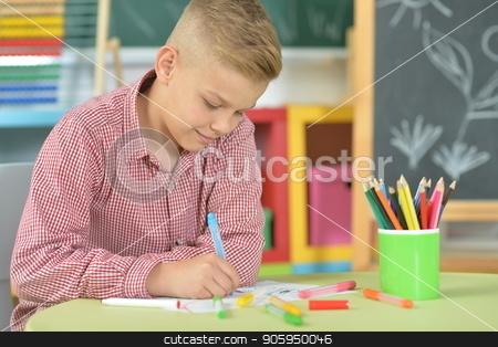 cute boy drawing stock photo, cute boy drawing with pencils in classroom by Ruslan Huzau