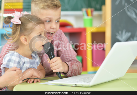 Brother and sister singing karaoke stock photo, Brother and sister singing karaoke with laptop at home by Ruslan Huzau