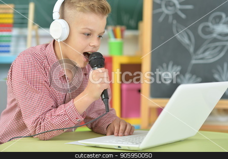 Teen boy in headphones singing karaoke stock photo, Teen boy in headphones singing karaoke with laptop in classroom by Ruslan Huzau
