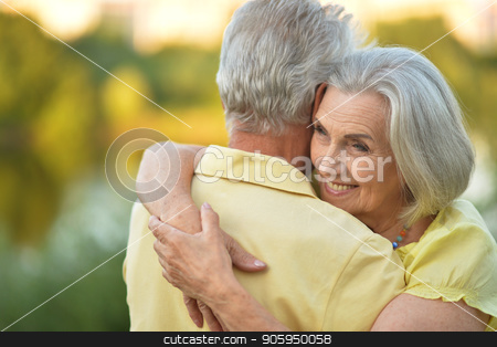 happy mature couple stock photo, happy senior couple smiling and hugging outdoors by Ruslan Huzau