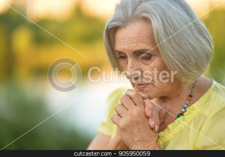 Portrait of beautiful sad senior woman stock photo, Portrait of beautiful sad senior woman  in summer park by Ruslan Huzau