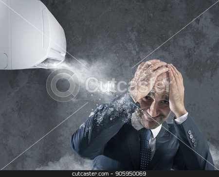Businessman tries to protect from himself icy air conditioner stock photo, Frozen businessman tries to protect himself from icy air conditioner by Federico Caputo