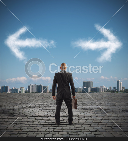 Confused businessman must choose the right way stock photo, Businessman in front of a choice with arrows in opposite directions by Federico Caputo