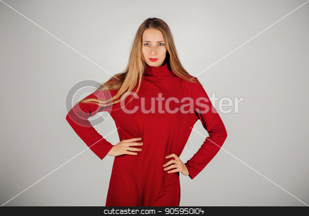 a beautiful girl with long hair in a red dress holds her hands on her side against a white background. Isolated photo of a female model stock photo, a beautiful girl with long hair in a red dress holds her hands on her side against a white background. Isolated photo of a female model by aaalll3110
