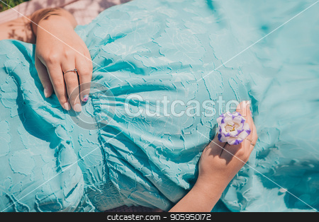 Pregnant woman in blue dress on flowers background stock photo, Pregnant woman in blue dress on flowers background by aaalll3110