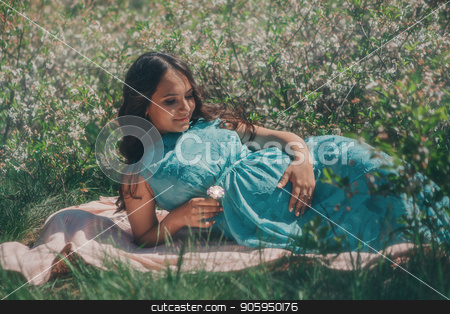 portrait of a young girl: a pregnant woman lying on the ground on a grass background stock photo, portrait of a young girl: a pregnant woman lying on the ground on a grass background by aaalll3110