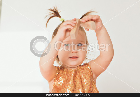 portrait of a little girl with tails on white background. Baby plays with toys stock photo, portrait of a little girl with tails on white background. Baby plays with toys by aaalll3110
