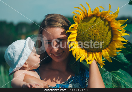 Portrait of a girl with baby and flower on a background of green foliage stock photo, Portrait of a girl with baby and flower on a background of green foliage by aaalll3110