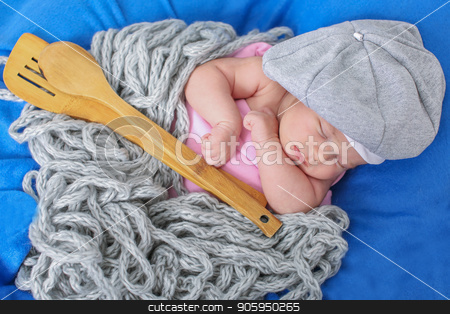 A little child in a grey cap lies witn a spoon on a blue background stock photo, A little child in a grey cap lies witn a spoon on a blue background by aaalll3110