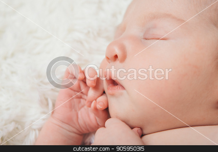 Face of sleeping newborn baby holding fist near mouth, close up on white background. Portrait of little girl stock photo, Face of sleeping newborn baby holding fist near mouth, close up on white background. Portrait of little girl by aaalll3110