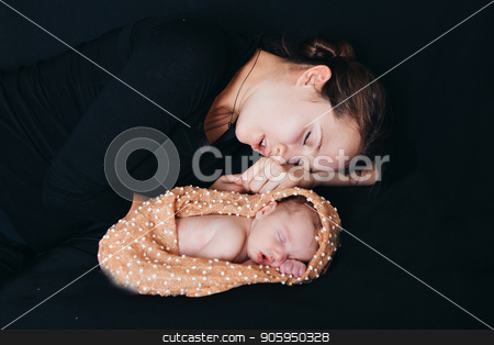 a woman and a newborn baby sleep on a black background. Mother and child stock photo, a woman and a newborn baby sleep on a black background. Mother and child by aaalll3110